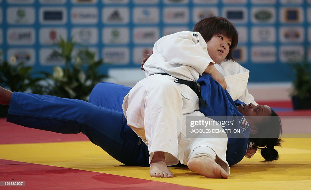 Japan's Tachimoto Migumi (white) fights against France's Rebecca Ramanich (blue) on February 10, 2013 in Paris, during the eliminatories of the Women + 78kg of the Paris Judo Grand Slam tournament.