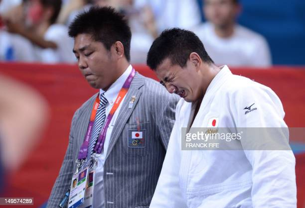 Japan's Takahiro Nakai leaves with his coach after losing against Russia's Ivan Nifontov during their men's 81kg judo contest bronze medal match of...