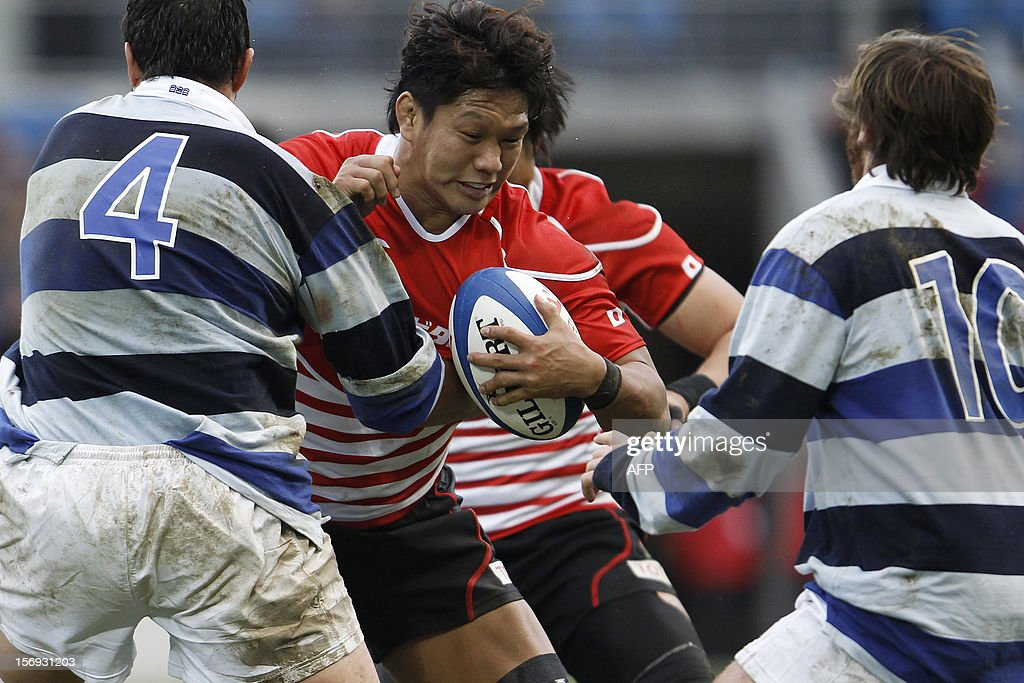 Japan's Takashi Kikutani is blocked by Barbarian's Matthias Rolland (L) during the Rugby Union exhibition match between Barbarian RC and Japan XV at Oceane Stadium, on November 25, 2012, in the northwestern city of Le Havre.