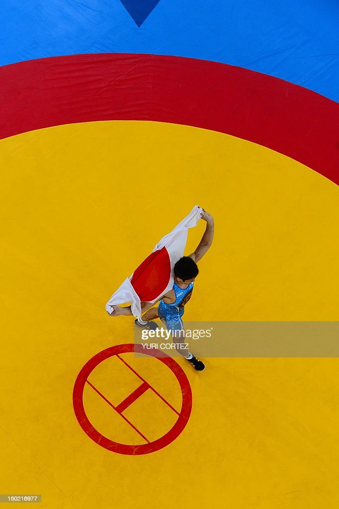 Japan's Tatsuhiro Yonemitsu celebrates with his national flag after winning the Men's 66kg Freestyle gold medal match on August 12 2012 during the...