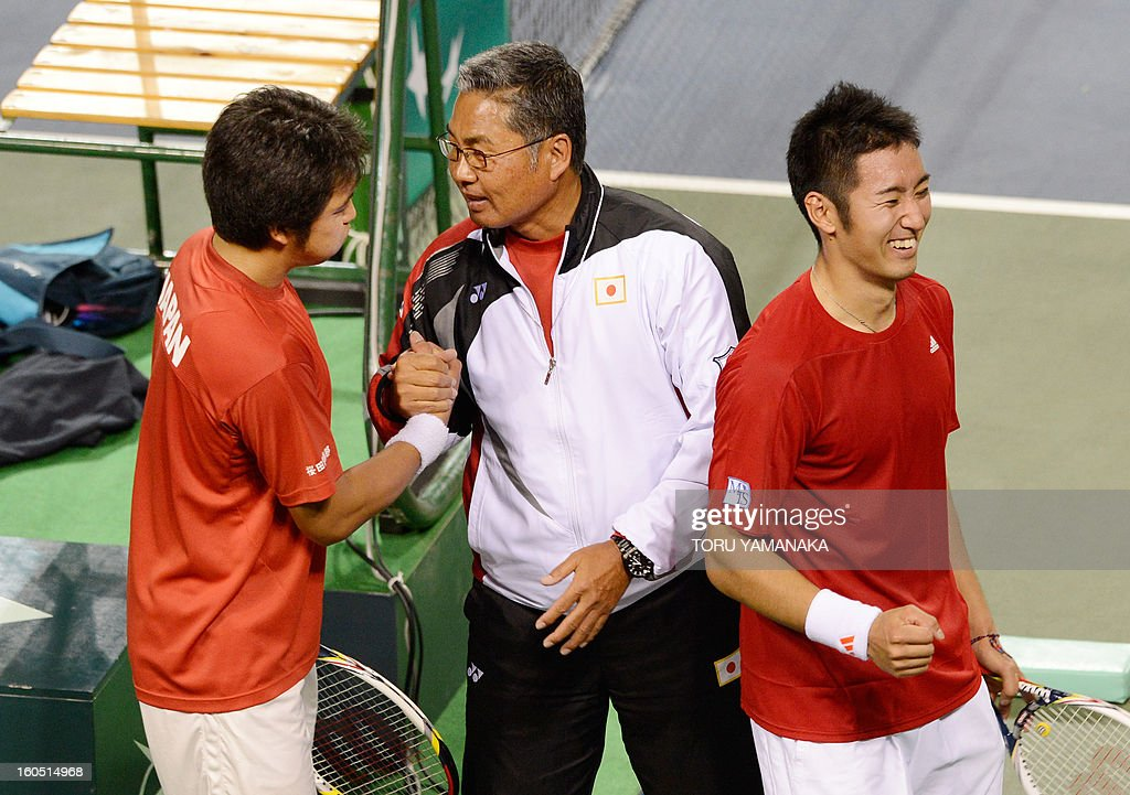 Japan's Tatsuma Ito (L) and Yasutaka Uchiyama (R) are congratulated by team captain Minoru Ueda (C) after their victory against Indonesia's Christopher Rungkat and Elbert Sie during their men's doubles tennis match at the Davis Cup Asia-Oceania Zone Group I first-round tie in Tokyo on February 2, 2013. AFP PHOTO/Toru YAMANAKA