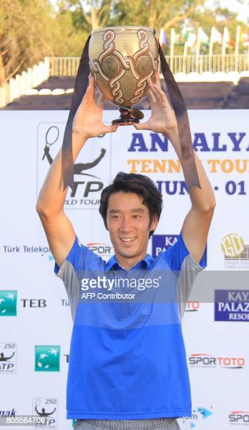 Japan's tennis player Yuichi Sugita celebrates as he poses with his trophy after winning the men's final match against French player Adrian Mannarino...