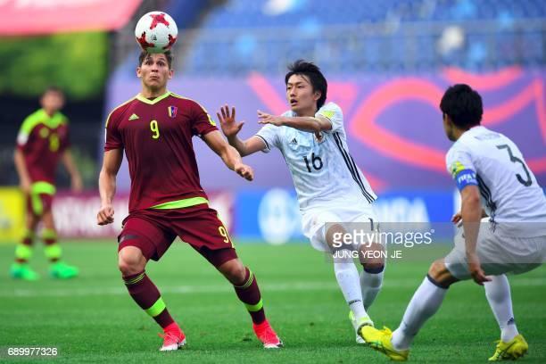 Japan's Teruki Hara fights for the ball with Venezuela's Ronaldo Pena as Japan's Yuta Nakayama watches during their U20 World Cup round of 16...