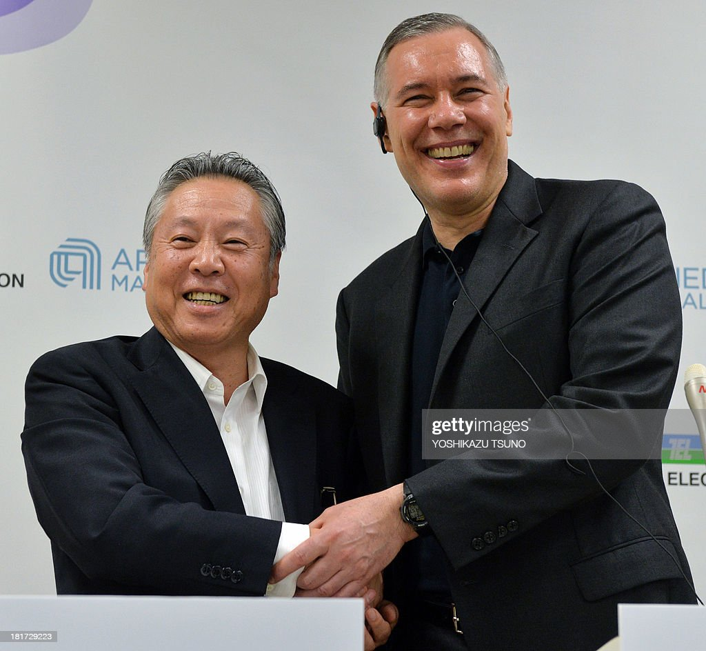 Japan's Tokyo Electron chairman Tetsuro Higashi (L) shakes hands with US semiconductor giant Applied Materials CEO Gary Dickerson (R) after they agreed to merge next year at a press conference at the Tokyo Electron headquarters in Tokyo on September 24, 2013. Applied Materials and Tokyo Electron, US and Japanese makers of tools to produce semiconductors and displays, said they will merge to increase efficiency and to better meet changing customer demands. AFP PHOTO / Yoshikazu TSUNO
