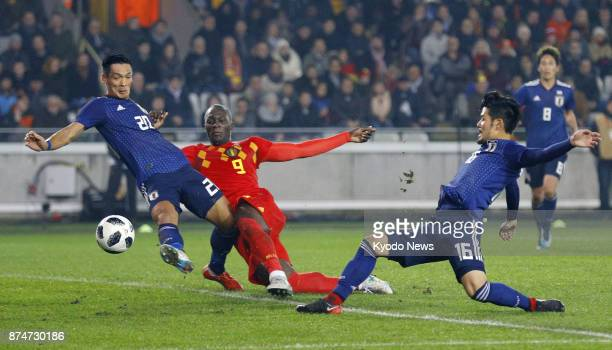 Japan's Tomoaki Makino and Hotaru Yamaguchi try to block Romelu Lukaku of Belgium during the first half of a friendly in Bruges Belgium on Nov 14...