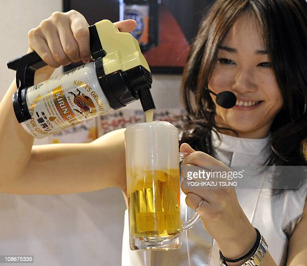 Japan's toy giant Tomy employee pours a canned beer with a toy beer server 'Beer Hour' which makes creamy froth on beer at the Tokyo International...