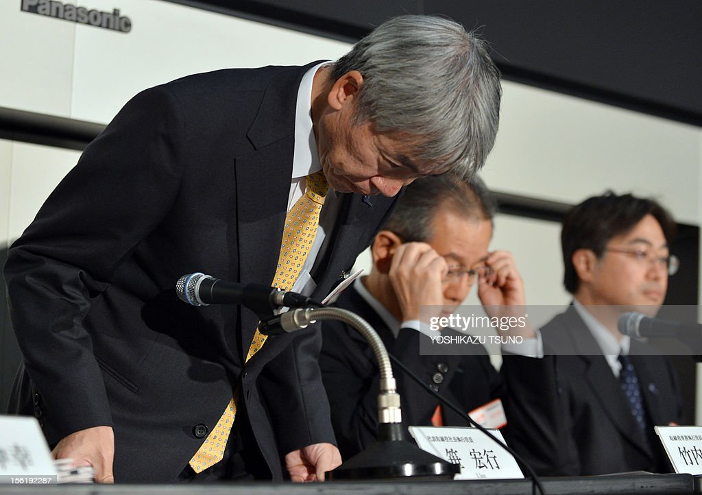 Japan's troubled optical giant Olympus president Hiroyuki Sasa (L) bows his head as he announces the company's first half financial result ended September at the Tokyo Stock Exchange on November 12, 2012. Olympus said on November 12 it had swung to a 100 million USD first-half profit, reversing a year-earlier loss, as the camera and medical equipment maker moves on from an embarrassing accounting scandal. AFP PHOTO / Yoshikazu TSUNO