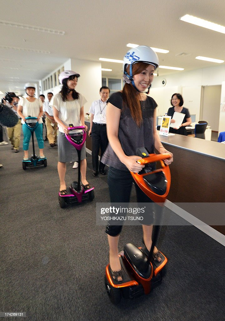 Japan's Tsukuba City Hall employees ride on Toyota's transport assistance robot, called the 'Winglet', during a demonstration in City Hall in Tsukuba City, suburban Tokyo on July 23, 2013. Toyota and Tsukuba City started to field test the next generation of 'personal mobility robot' on the public thoroughfare, with trial runs scheduled until 2016. AFP PHOTO / Yoshikazu TSUNO