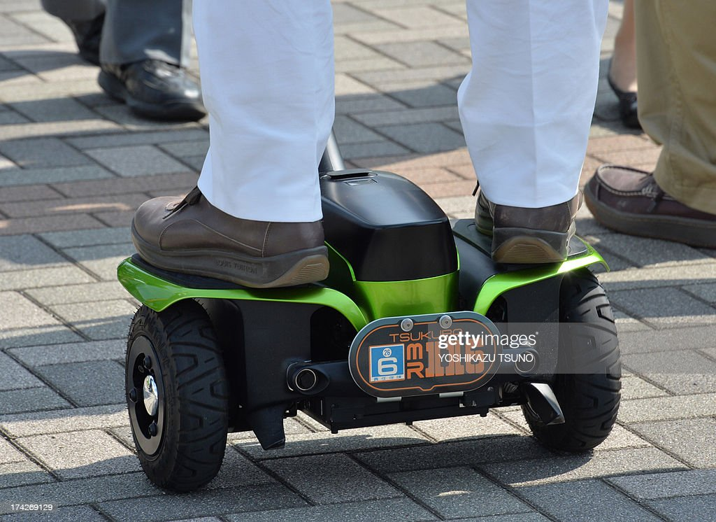 Japan's Tsukuba City Mayor Kenichi Ichihara rides on Toyota's transport assistance robot, called the 'Winglet', during a demonstration on a public sidewalk in Tsukuba City, suburban Tokyo on July 23, 2013. Toyota and Tsukuba City started to field test the next generation of 'personal mobility robot' on the public thoroughfare, with trial runs scheduled until 2016. AFP PHOTO / Yoshikazu TSUNO
