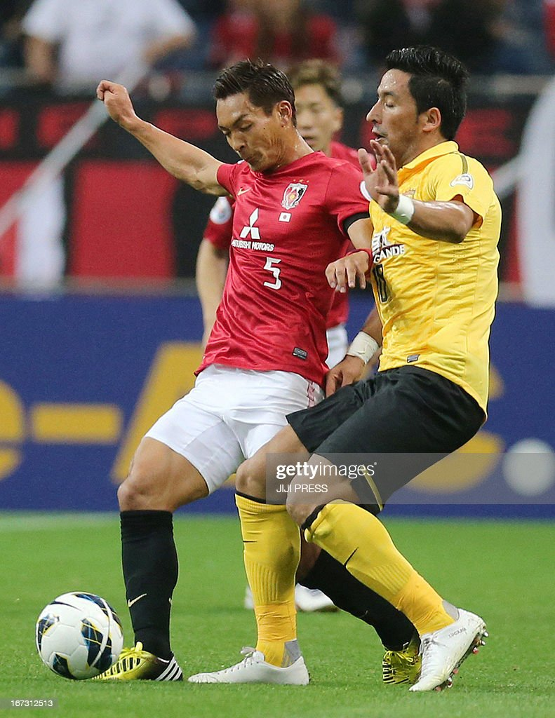 Japan's Urawa Red Diamonds defender Tomoaki Makino (L) fights for the ball against China's Guangzhou Evergrande forward Lucas Barrios during their AFC Champions League group F match in Saitama, suburban Tokyo on April 24, 2013. Urawa defeated Guangzhou 3-2. AFP PHOTO / JIJI PRESS JAPAN OUT