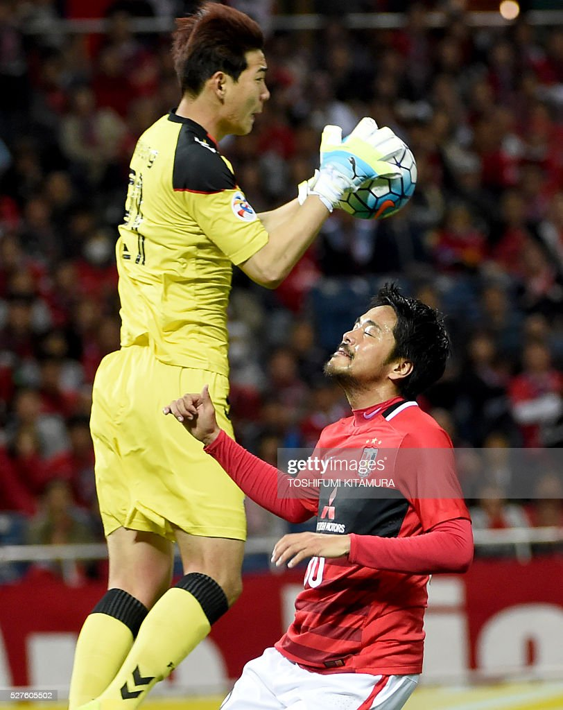 Japan's Urawa Reds midfielder Shinzo Koroki (R) dejects while South Korea's Pohang Steelers goalkeeper Kim Jin-Young (L) catching the ball during their AFC champions league group H football match in Saitama on May 3, 2016. / AFP / TOSHIFUMI