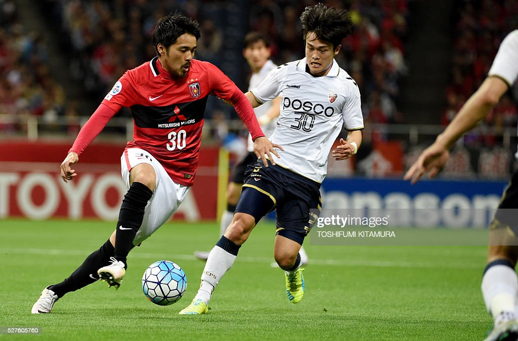 Japan's Urawa Reds midfielder Shinzo Koroki (L) dribbles the ball beside South Korea's Pohang Steelers forward Jung Wonjin (R) during their AFC champions league group H football match in Saitama on May 3, 2016. / AFP / TOSHIFUMI