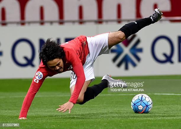 Japan's Urawa Reds midfielder Shinzo Koroki falls on the pitch after colliding with Australia's Sydney FC goalkeeper Jedran Janjetovic to get a...