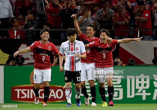 Japan's Urawa Reds midfielder Tomoya Ugajin celebrates his goal with midfielder Yuki Muto and forward Tadanori Lee behind South Korea's FC Seoul...