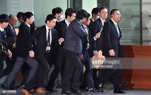 Japan's Vice Foreign Minister Akitaka Saiki is surrounded by reporters as he leaves the prime minister's official residence in Tokyo on January 25...