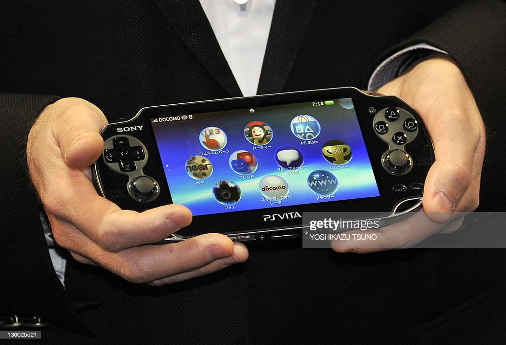 Japan's video game giant Sony Compuer Entertainment (SCE) president Andrew House displays the new portable video game console 'PlayStation Vita' (PS Vita) at the launching event in a video game shop in Tokyo on December 17, 2011. Sony will put the new gaming system on the market in the United States and Europe in February 2012. AFP PHOTO / Yoshikazu TSUNO