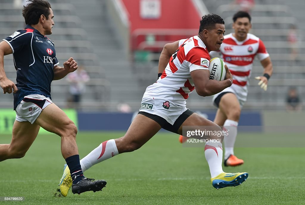 Japan's wing Ataata Moeakiola (R) runs with the ball during their Asia Rugby Championship match against Hong Kong at the Prince Chichibu Memorial Rugby Ground in Tokyo on May 28, 2016. / AFP / KAZUHIRO