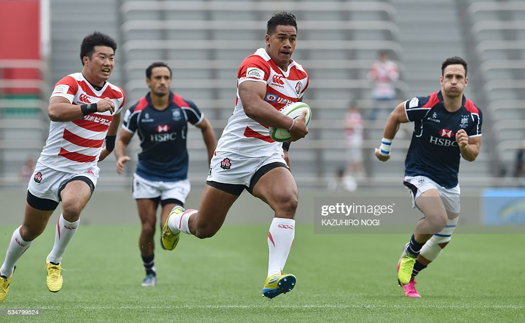 Japan's wing Ataata Moeakiola (C) runs with the ball during their Asia Rugby Championship match against Hong Kong at the Prince Chichibu Memorial Rugby Ground in Tokyo on May 28, 2016. / AFP / KAZUHIRO