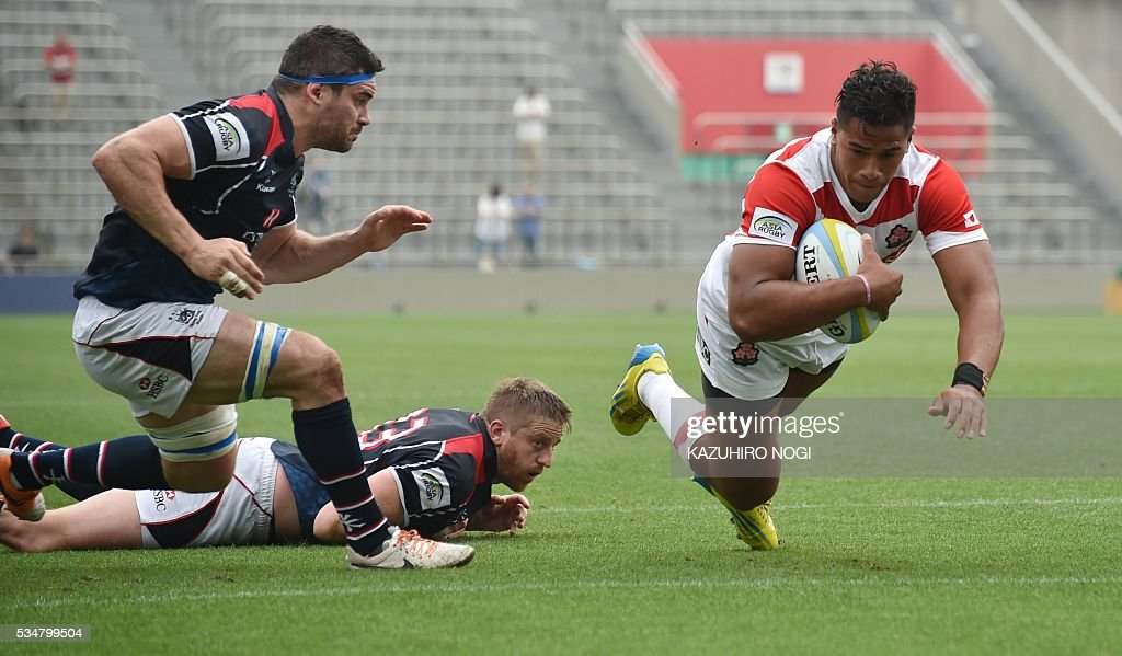 Japan's wing Ataata Moeakiola (R) scores a try past Hong Kong's flanker Matthew Lamming (L) during their Asia Rugby Championship match at the Prince Chichibu Memorial Rugby Ground in Tokyo on May 28, 2016. / AFP / KAZUHIRO