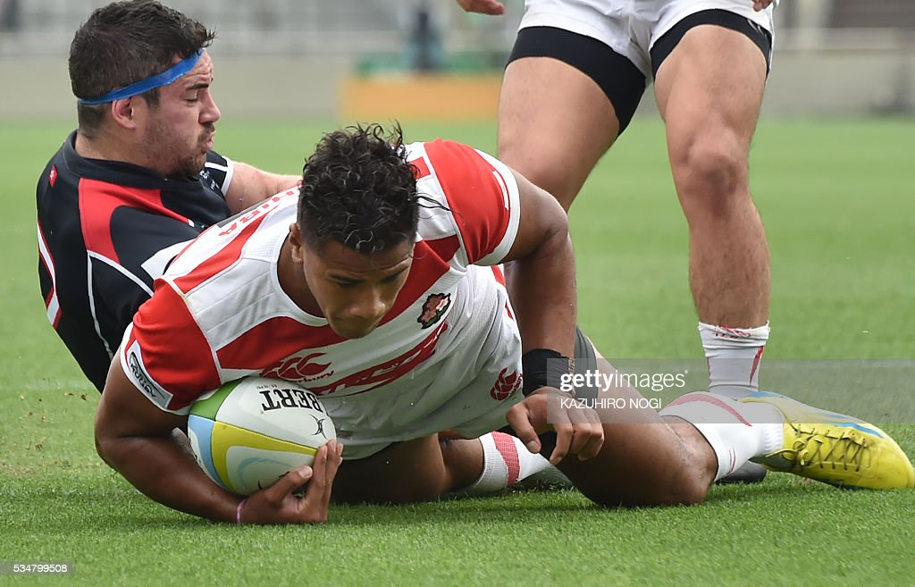 Japan's wing Ataata Moeakiola (C) scores a try past Hong Kong's flanker Matthew Lamming (L) during their Asia Rugby Championship match at the Prince Chichibu Memorial Rugby Ground in Tokyo on May 28, 2016. / AFP / KAZUHIRO