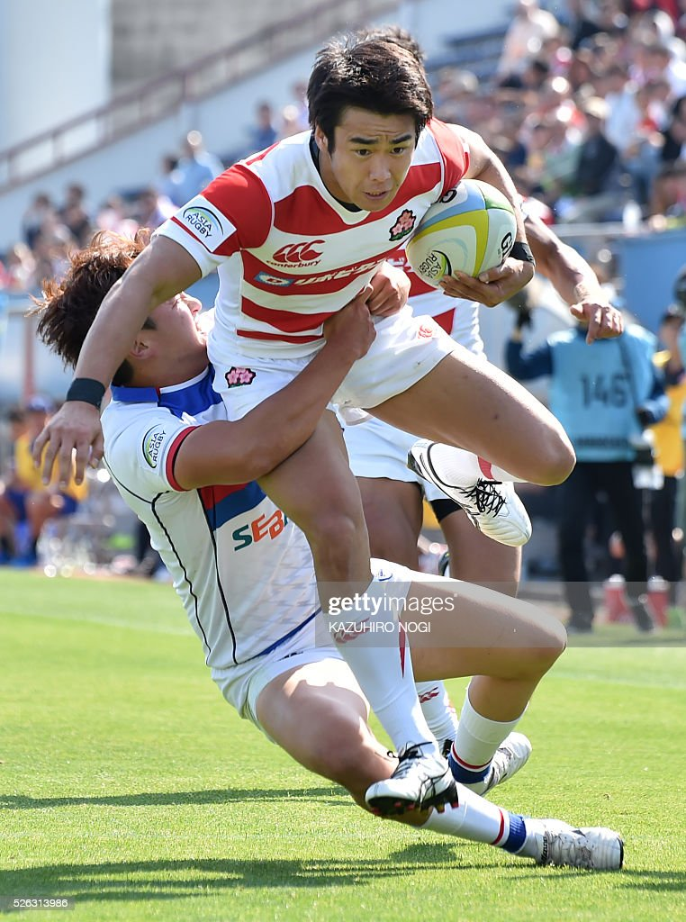 Japan's wing Kentaro Kodama (R) is tackled by South Korea's full-back Nam Young Soo (L) during their Asian Rugby Championship rugby match in Yokohama on April 30, 2016. / AFP / KAZUHIRO