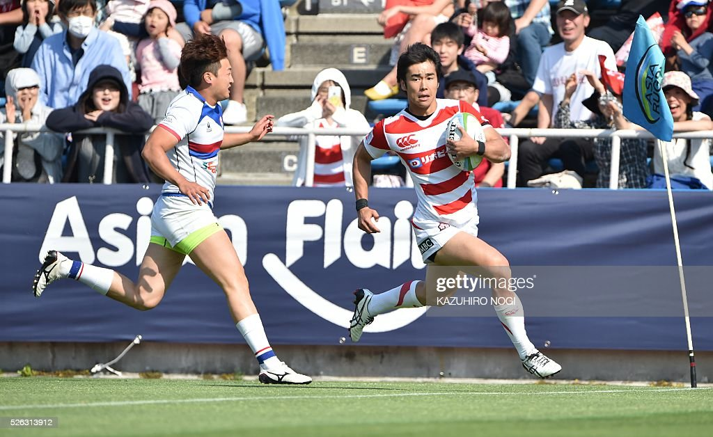 Japan's wing Kentaro Kodama (R) scores a try past South Korea's full-back Nam Young Soo (L) during their Asian Rugby Championship rugby match in Yokohama on April 30, 2016. / AFP / KAZUHIRO
