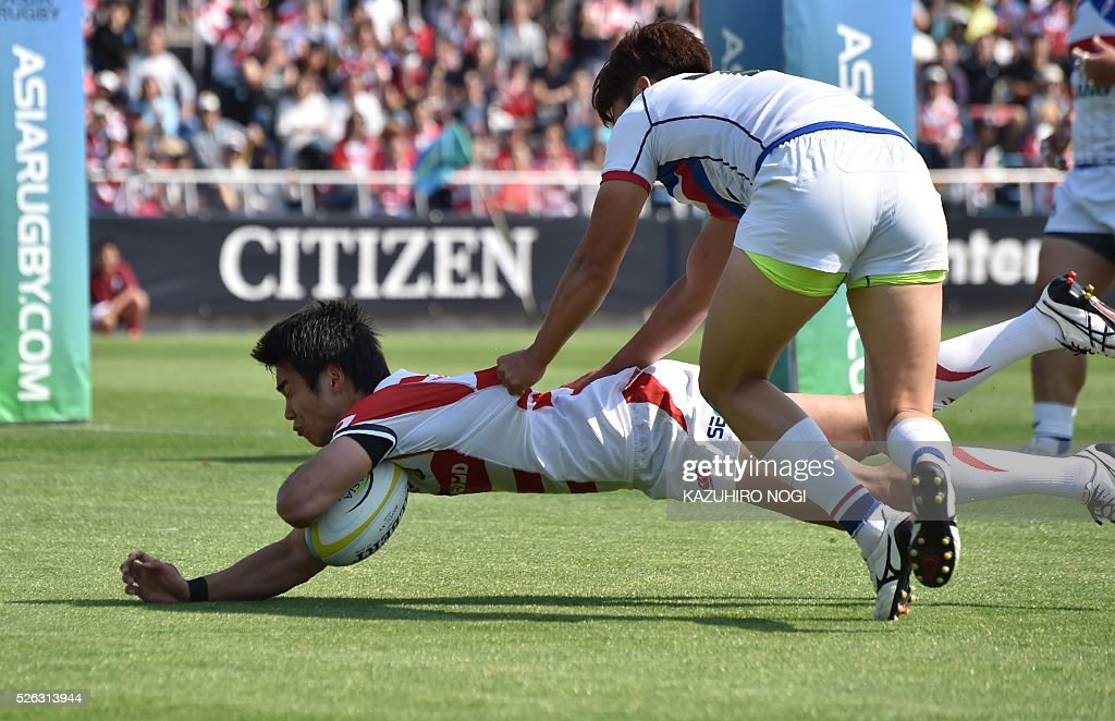 Japan's wing Kentaro Kodama (L) scores a try past South Korea's full-back Nam Young Soo (R) during their Asian Rugby Championship rugby match in Yokohama on April 30, 2016. / AFP / KAZUHIRO