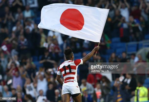 Japan's wing Kotaro Matsushima waves the Japanese national flag as the team celebrate their victory in the Pool B match of the 2015 Rugby World Cup...