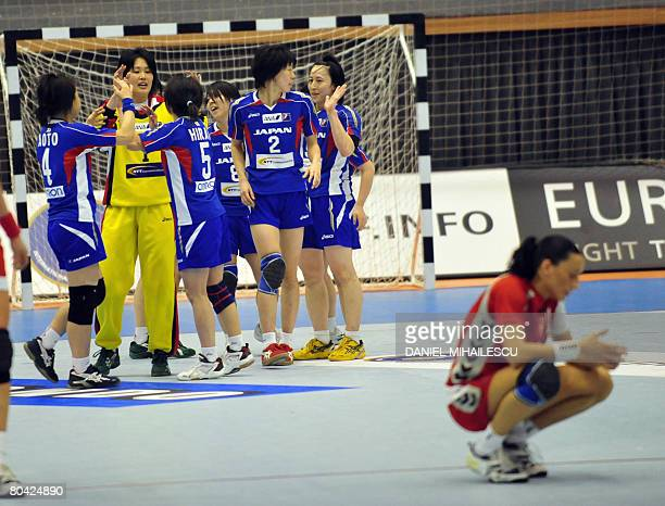 Japan's women handball team celebrate at the end of their Women Handball 2008 Olympic qualification tournament match against Poland as Polish player...