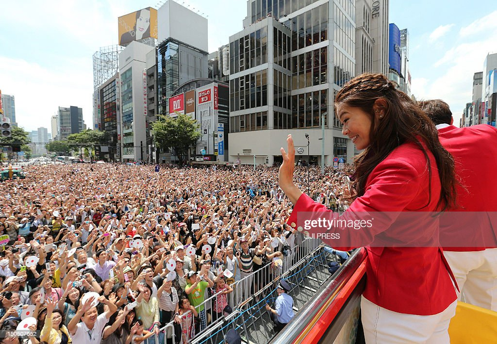Japan's women's football silver medallist Homare Sawa (R) waves to crowds of people from an open-top bus during a parade by Japan's 2012 London Olympic Games medallists at Tokyo's upmarket Ginza street on August 20, 2012. The Japan Olympic Committee (JOC) held the first ever Olympic medallists parade hoping it will boost the city's bid to host the 2020 Summer Games. JAPAN OUT AFP PHOTO / JAPAN POOL via JIJI PRESS