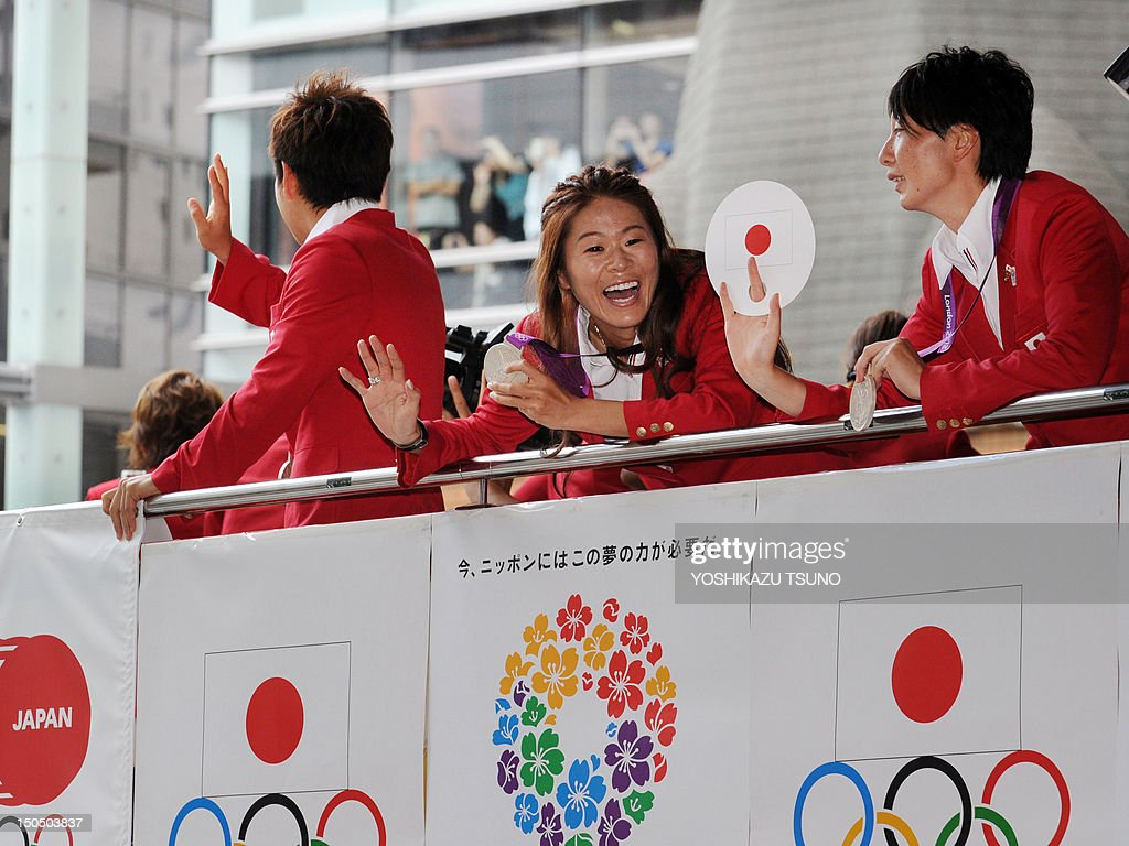 Japan's women's football team member and silver medallist, Homare Sawa (C), and other Japanese medalists at the London 2012 Olympic Games wave to the crowds from open-top buses during a parade at Tokyo's upmarket Ginza street on August 20, 2012. The Japan Olympic Committee (JOC) held the first ever Olympic medallists parade hoping it will boost the city's bid to host the 2020 Summer Games. AFP PHOTO / Yoshikazu TSUNO
