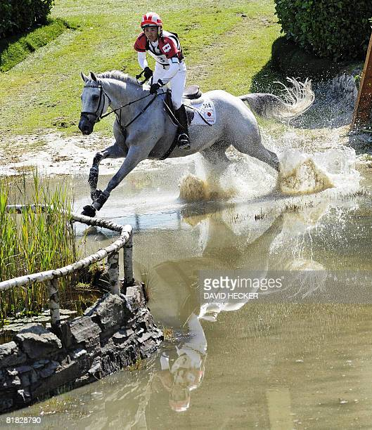 Japan's Yoshiaki Oiwa and his horse 'Gorgeous George' ride through the water after a jump during the CHIO World Equestrian Festival in Aachen western...