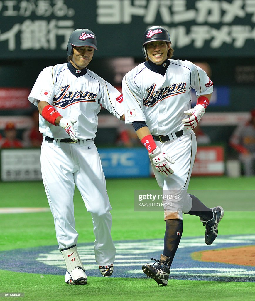 Japan's Yoshio Itoi is congratulated by teammate Atsunori Inaba after scoring against China during the second inning of the World Baseball Classic...
