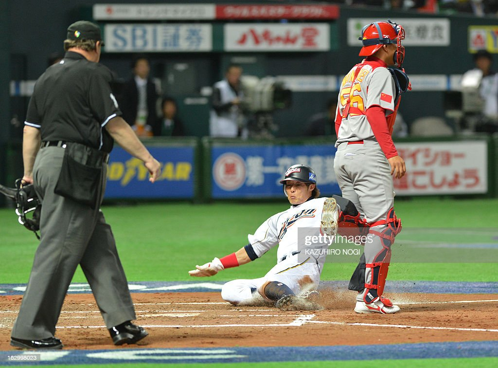 Japan's Yoshio Itoi scores as China's Catcher Wang Wei looks on during the second inning of the World Baseball Classic firstround game in Pool A in...