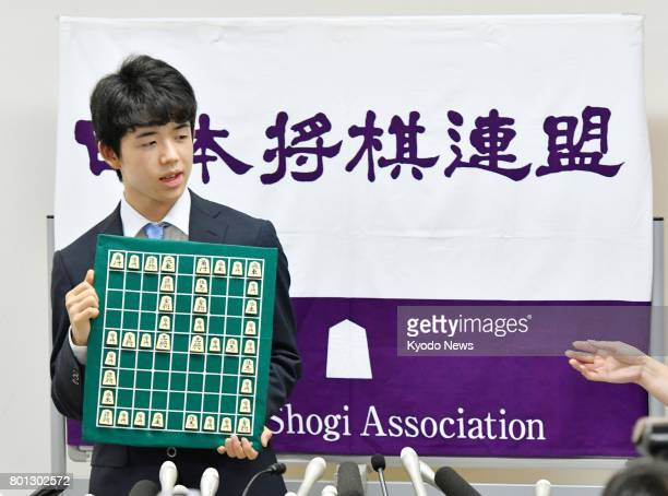 Japan's youngest professional shogi player 14yearold Sota Fujii holds a shogi board with the number 29 portrayed with shogi pieces at the Shogi...