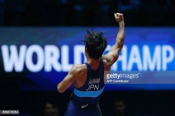 Japan's Yuhi Fujinami celebrates after winning the men's freestyle wrestling 70kg category bronze medal final at the FILA World Wrestling...