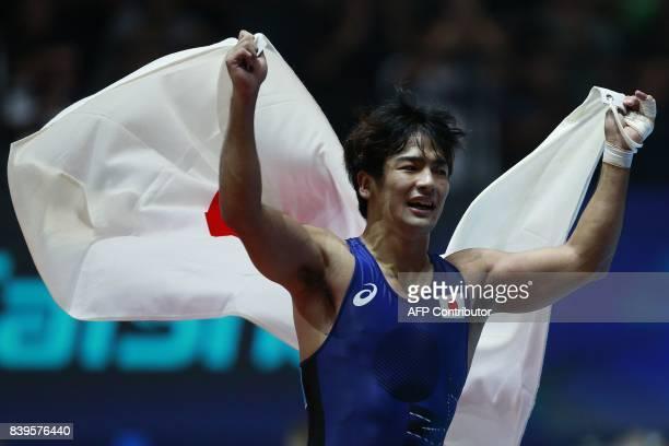 Japan's Yuhi Fujinami celebrates after winning the men's freestyle wrestling 70kg category bronze medal final at the FILA World Wrestling...