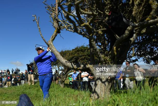 Japan's Yusaku Miyazato plays from behind a tree on the 6th hole during his opening round on the first day of the Open Golf Championship at Royal...