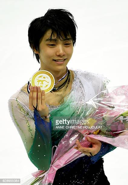 Japan's Yuzuru Hanyu celebrates on the podium after winning the senior Men Free program at the ISU Grand Prix of figure skating Final on December 10...
