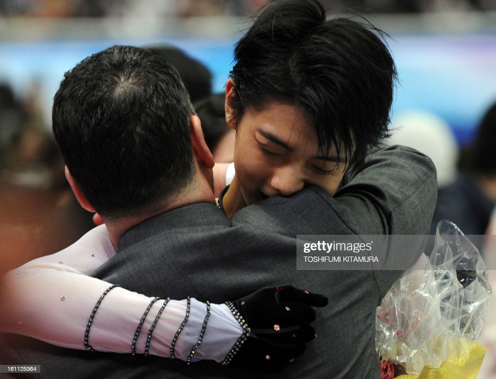 Japan's Yuzuru Hanyu (R) is congraturated by his coach after his free skating performance in the men's event during the Four Continents figure skating championships in Osaka on February 9, 2013.
