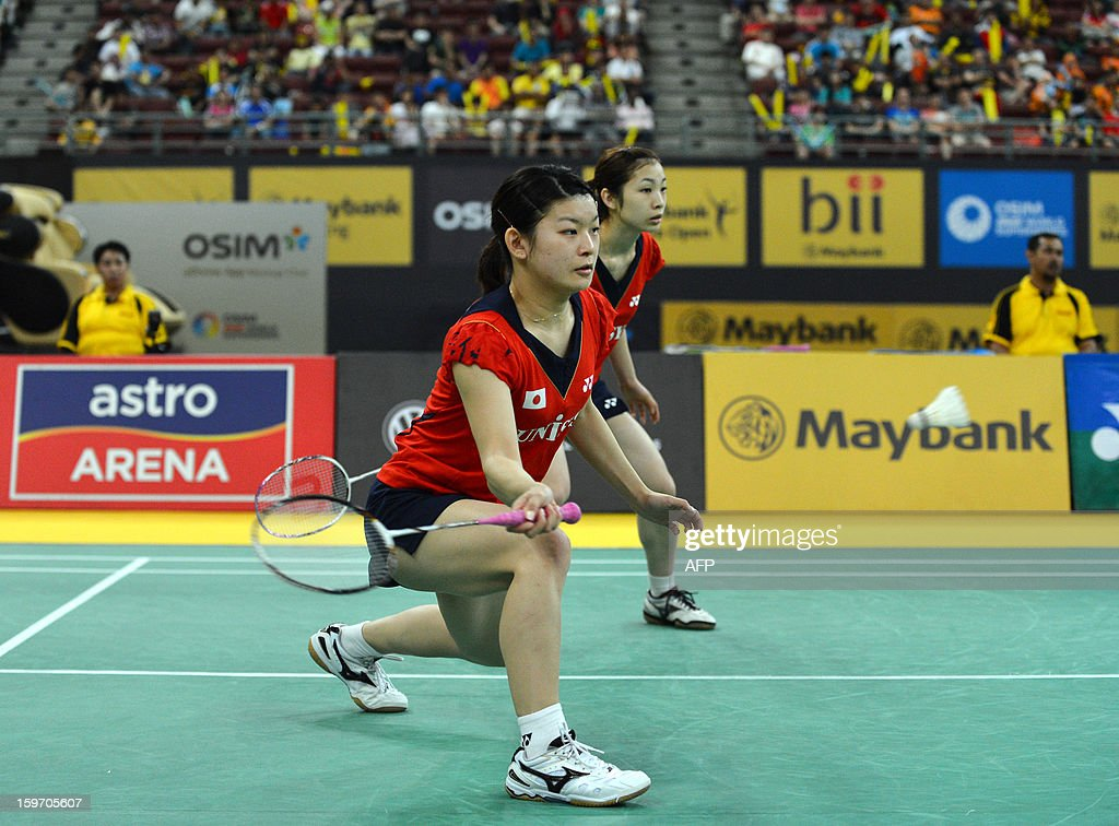 Japans's Ayaka Takahashi (L) hits a shot as partner Misaki Matsutomo looks on as they play against Singapore's Shinta Mulia Sari and Lei Yao during their woman's doubles semi-finals match of the Malaysia Open Badminton Superseries in Kuala Lumpur on January 19, 2013. AFP PHOTO / MOHD RASFAN