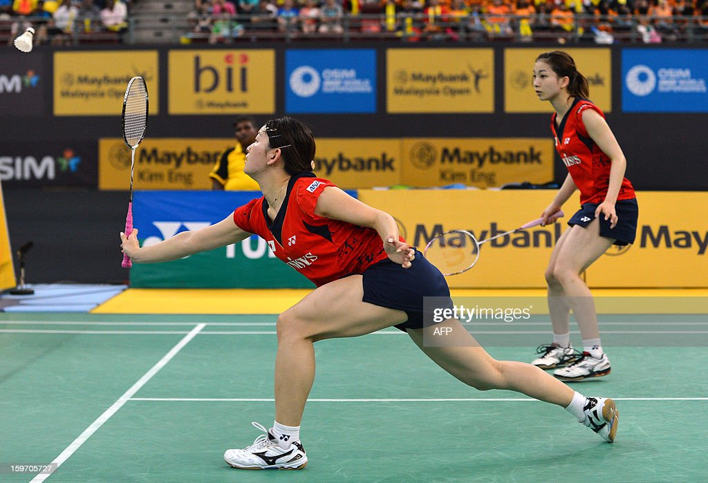Japans's Ayaka Takahashi (L) reaches for a return as partner Misaki Matsutomo (R) looks on as they play against Singapore's Shinta Mulia Sari and Lei Yao during their woman's doubles semi-finals match at the Malaysia Open Badminton Superseries in Kuala Lumpur on January 19, 2013.