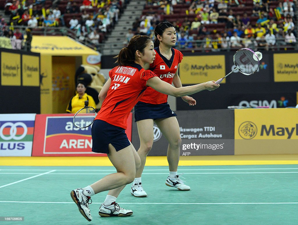 Japans's Misaki Matsutomo (L) hits a shot as partner Ayaka Takahashi looks on as they play against Singapore's Shinta Mulia Sari and Lei Yao during their woman's doubles semi-finals match at the Malaysia Open Badminton Superseries in Kuala Lumpur on January 19, 2013.