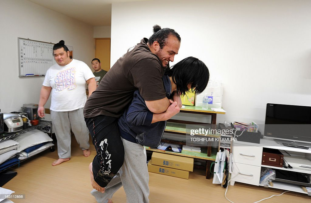 Japan-sumo-society-JPN,FEATURE by Shigemi Sato This photo taken on February 14, 2013 shows sumo wrestler Osunaarashi of Egypt (C) joking around with fellow wrestler Ginseizan (R) after a training session at a sumo stable in Tokyo. Most of the 610 wrestlers who come under the aegis of the venerable Japan Sumo Association are lodged in stables like this one; living, eating and sleeping together in facilities that allow for little personal space. Osunaarashi, who's real name is Abdelrahman Ahmed Shaalan, is the highest ranked wrestler amongst stablemaster Tadahiro Otake's eight wrestlers, who needs to climb 23 ranks to crack into the second division. AFP PHOTO / TOSHIFUMI KITAMURA