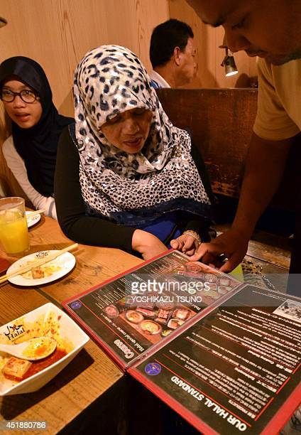 JapantourismreligionIslamFEATURE This picture taken on June 24 2014 shows Thai Muslim tourists checking a menu of Halal certified foods at a barbecue...