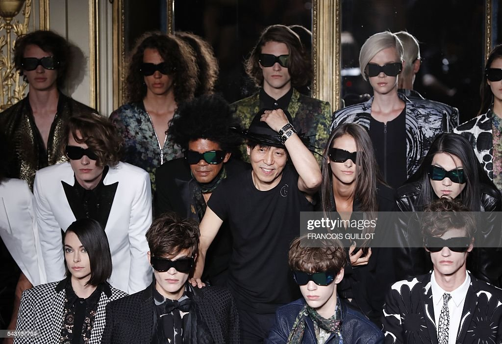 Japonese fashion designer Rynshu (C) poses with models at the end of the men's Spring/Summer 2017 collection fashion show on June 26, 2016 in Paris. / AFP / FRANCOIS
