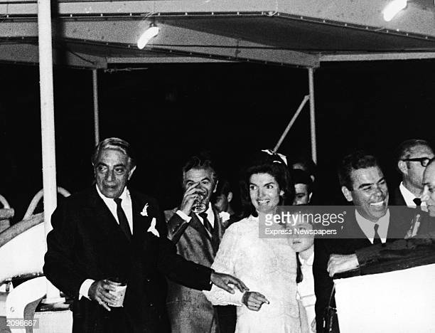 Jaqueline Kennedy Onassis embracing her daughter Caroline Kennedy and her new husband Greek shipping magnate Aristotle Onassis hold a reception...
