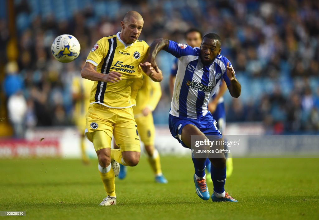 Jaques Maghoma of Sheffield Wednesday battles with Alan Dunne of Millwall during the Sky Bet Championship match between Sheffield Wednesday and Millwall at Hillsborough Stadium on August 19, 2014 in Sheffield, England.