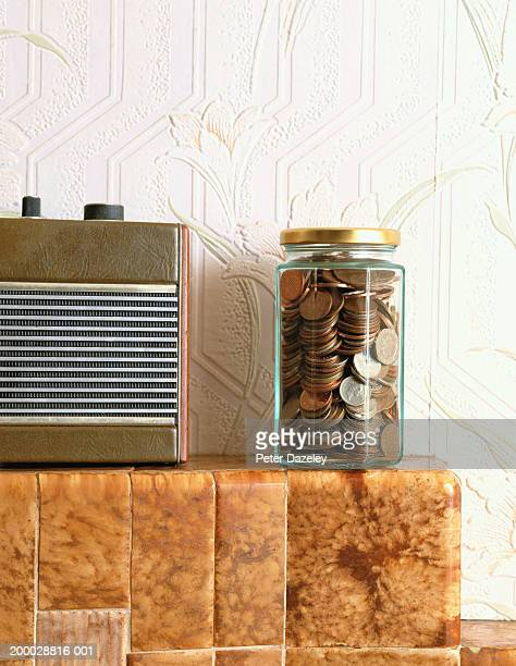 Jar of assorted coins on mantlepiece beside radio, close-up
