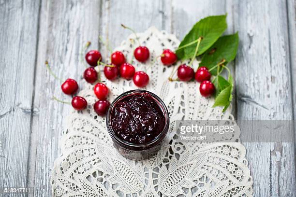 Jar of cherry jam and cherries on dolly